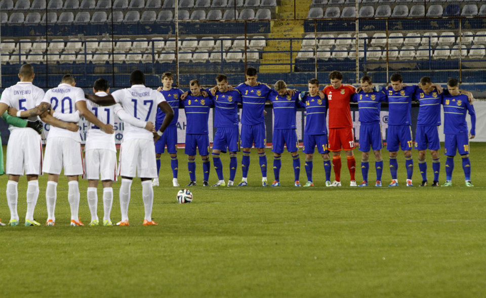 Photo - Players of Ukraine, right, and U.S. hold a minute's silence in honor of victims of recent violent clashes in the Ukrainian capital before the start of their international friendly match at Antonis Papadopoulos stadium in southern city of Larnaca, Cyprus, Wednesday, March 5, 2014. The Ukrainians are facing the United States in a friendly on Wednesday in Cyprus, a match moved from Kharkiv to Larnaca for security reasons. (AP Photo/Petros Karadjias)