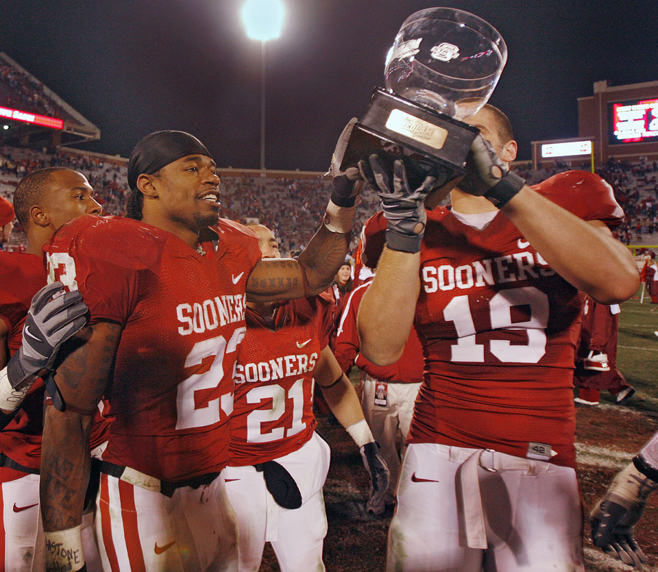 Photo - Oklahoma's Allen Patrick (23) and Joe Jon Finley (19) celebrate with the Bedlam Trophy after defeating Oklahoma State 49-17 in the college football game between the University of Oklahoma Sooners (OU) and the Oklahoma State University Cowboys (OSU) at the Gaylord Family-Memorial Stadium on Saturday, Nov. 24, 2007, in Norman, Okla. 
