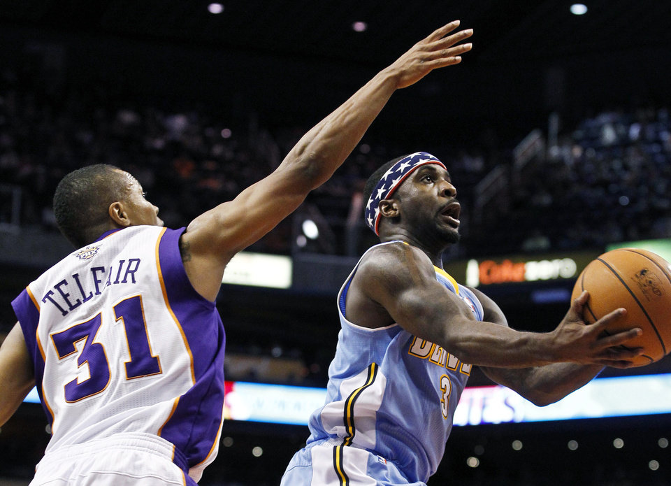 Denver Nuggets' Ty Lawson (3) looks to shoot under pressure from Phoenix Suns' Sebastian Telfair (31) in the first half during an NBA basketball game on Monday, Nov. 12, 2012, in Phoenix. (AP Photo/Ross D. Franklin)