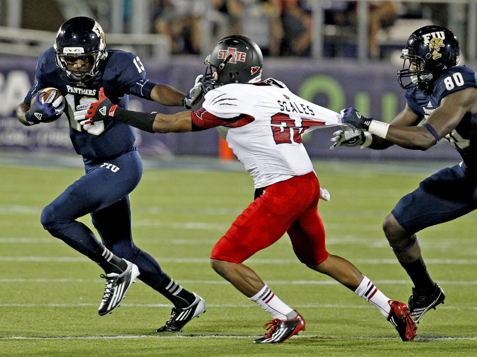 Florida International quarterback E.J. Hillard, left, stiff-arms Arkansas State\'s Chaz Scales as FIU\'s Ya\'keem Griner draws a penalty for holding in the second quarter of an NCAA college football game at FIU Stadium in Miami, Thursday, Oct. 4, 2012. (AP Photo/The Miami Herald, Charles Trainor Jr.) MAGAZINES OUT