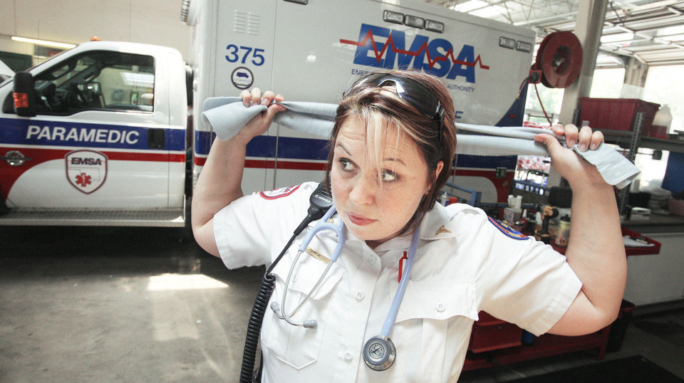 Photo - EMSA paramedic Tori Spencer ties a cooling towel around her neck Tuesday in Oklahoma City. EMSA issued the cooling towels to staff members to help them stay cool during the heat wave.  Photo by Paul B. Southerland, The Oklahoman