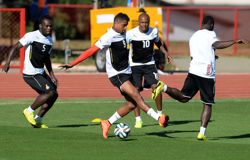 Photo - Ghana's Michael Essien, Kevin Prince Boateng and Andre Ayew, from left to centre, challenge for the ball during a training session in Brasilia, Brazil, Wednesday, June 25, 2014. Ghana will play Portugal in group G of the 2014 soccer World Cup on June 26. (AP Photo/Paulo Duarte)