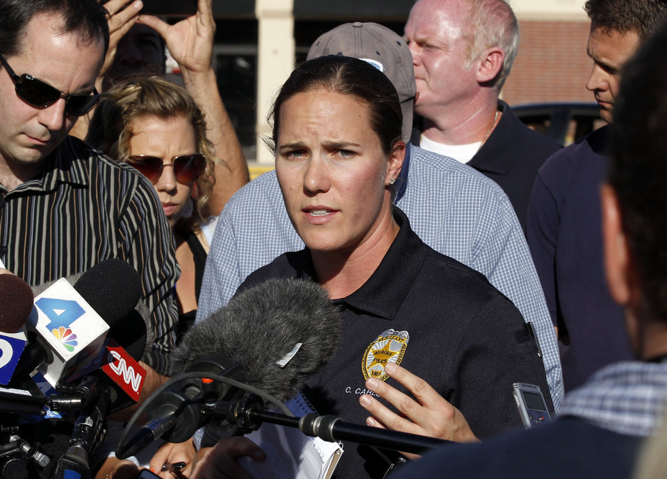 Photo -   Sgt. Cassidy Carlson, center, spokesperson for the Aurora Police Department, speaks during a media availability near the apartment of alleged gunman James Holmes, Saturday, July 21, 2012, in Aurora, Colo. Authorities reported that 12 people died and dozens more were shot during an assault at a movie theater midnight premiere of