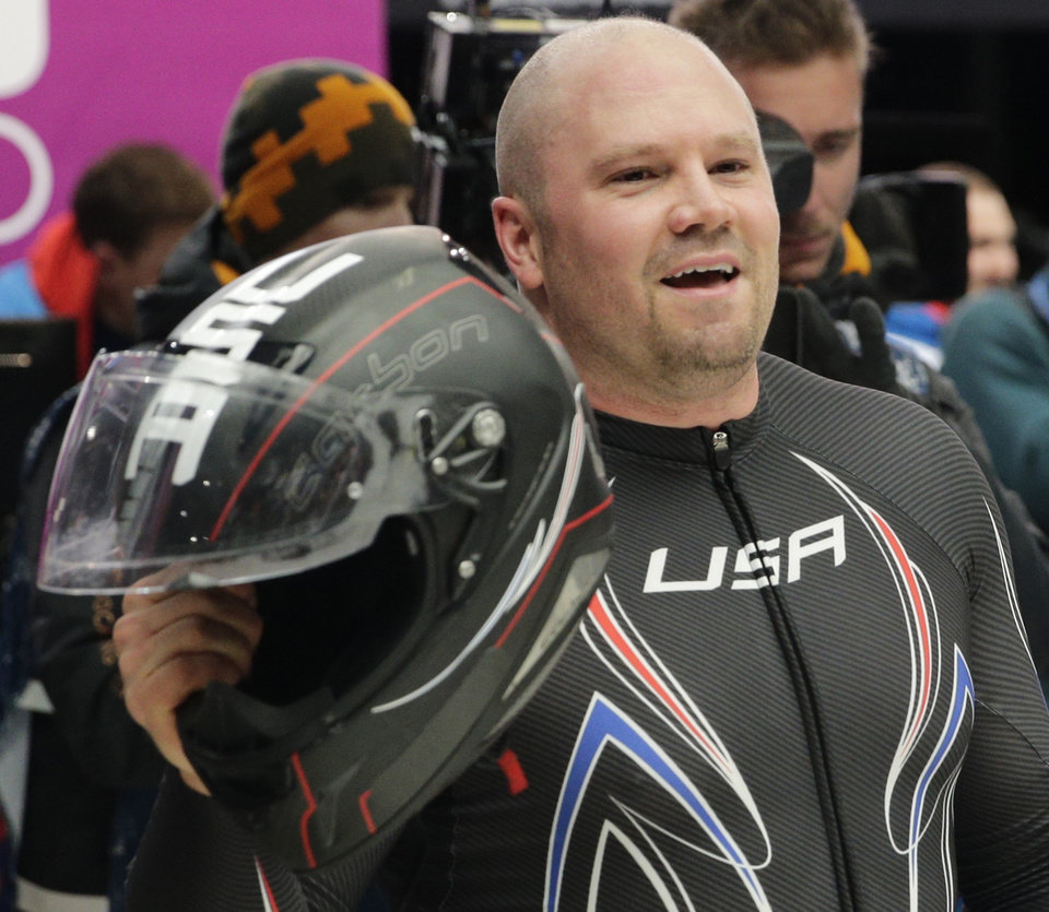Photo - The pilot from the United States USA-1, Steven Holcomb celebrates his bronze medal win in the men's two-man bobsled competition at the 2014 Winter Olympics, Monday, Feb. 17, 2014, in Krasnaya Polyana, Russia. (AP Photo/Jae C. Hong)