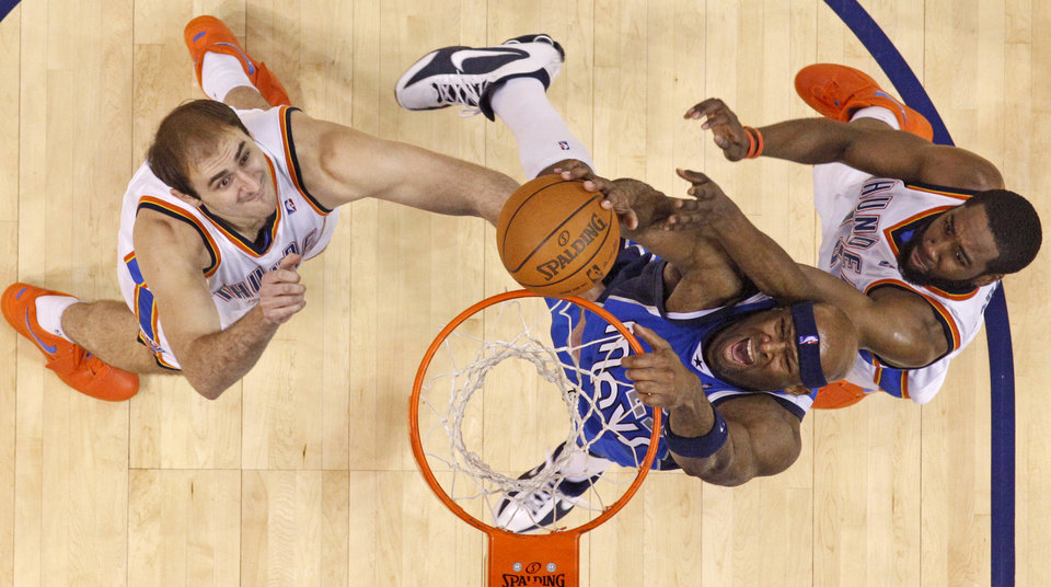 Photo - Erick Dampier of Dallas goes to the basket between Oklahoma City's Nenad Krstic, left, and James Harden during the NBA basketball game between the Oklahoma City Thunder and the Dallas Mavericks at the Ford Center in Oklahoma City on Wednesday, December 16, 2009. Photo by Bryan Terry, The Oklahoman