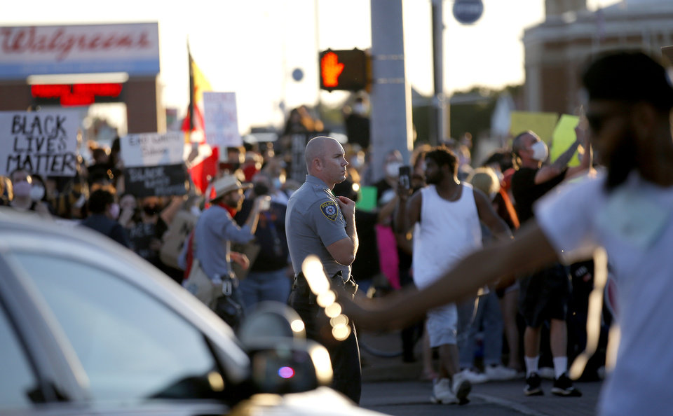 Photo - An Oklahoma Police officer stands in the the intersection of 23rd and Classen during a protest in Oklahoma City, Saturday, May 30, 2020. The protest was in response to the death of George Floyd. [Sarah Phipps/The Oklahoman]