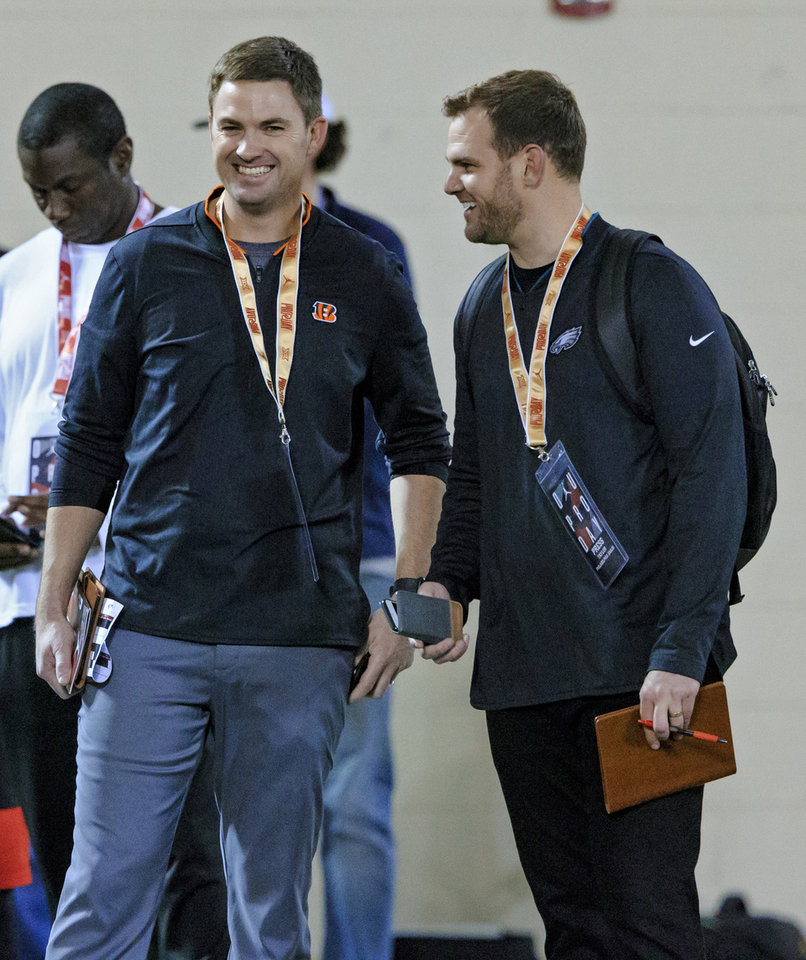 Photo - Cincinnati Bengal coach Zac Taylor, left, and his brother Philadelphia Eagles quarterback coach Press Taylor talk during the University of Oklahoma football pro day at the University of Oklahoma in Norman, Okla. on Wednesday, March 13, 2019.   Photo by Chris Landsberger, The Oklahoman