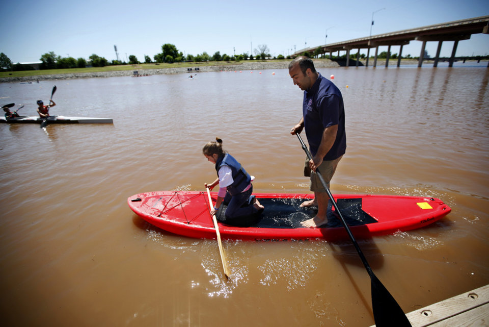 Aasim Saleh helps Reagan Cook, 8, of Midwest City, Okla.,  try out a paddle boat during the Paddle Now! Youth Experience on the Oklahoma River,  Saturday, April 21, 2012. Photo by Sarah Phipps, The Oklahoman.
