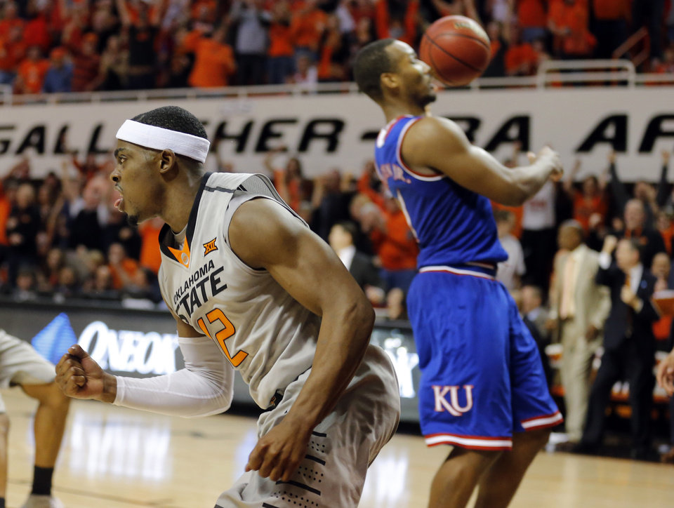 Photo - Oklahoma State's Anthony Hickey Jr. (12) celebrates a basket in front of Kansas' Kelly Oubre Jr. (12) during the men's college basketball game between Oklahoma State University and the University of Kansas at Gallagher-Iba Arena in Stillwater, Okla.,  Saturday, Feb. 7, 2015. OSU won 67-62. Photo by Sarah Phipps, The Oklahoman