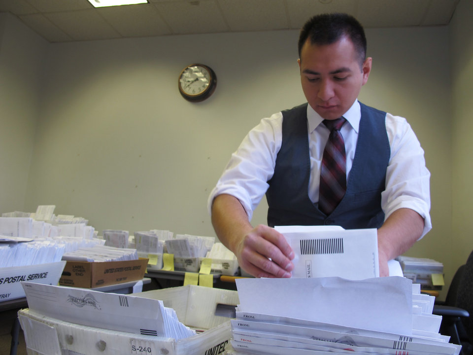 Marcelo Guardiola, a Milwaukee Election Commission staffer, sorts absentee ballots on Monday, Nov. 5, 2012 in Milwaukee. The Election Commission is sorting a record 50,000 absentee ballots this year. (AP Photo/Carrie Antlfinger)