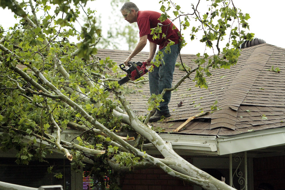Photo - A homeowner cuts a tree from his roof after damage from a tornado that struck the west and central parts of town Friday, April 13, 2012, in Norman, Okla. In an unusually early and strong warning, national weather forecasters cautioned Friday that conditions are ripe for violent tornadoes to rip through the nation from Texas to Minnesota this weekend.  (AP Photo/The Oklahoman, Steve Sisney) TABLOIDS OUT ORG XMIT: OKOKL107