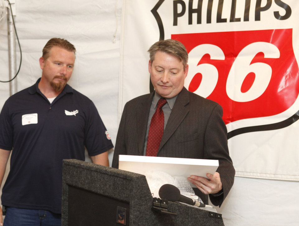 Photo - OSHA Area Director David Bates reads the inscription on a plaque Tuesday before passing it to Oklahoma City Pipeline Supervisor Steven Derk as Phillips 66 celebrates a safety program achievement with OSHA at their      facility on NE 10 in Oklahoma City. Photo by Paul Hellstern, The Oklahoman  PAUL HELLSTERN