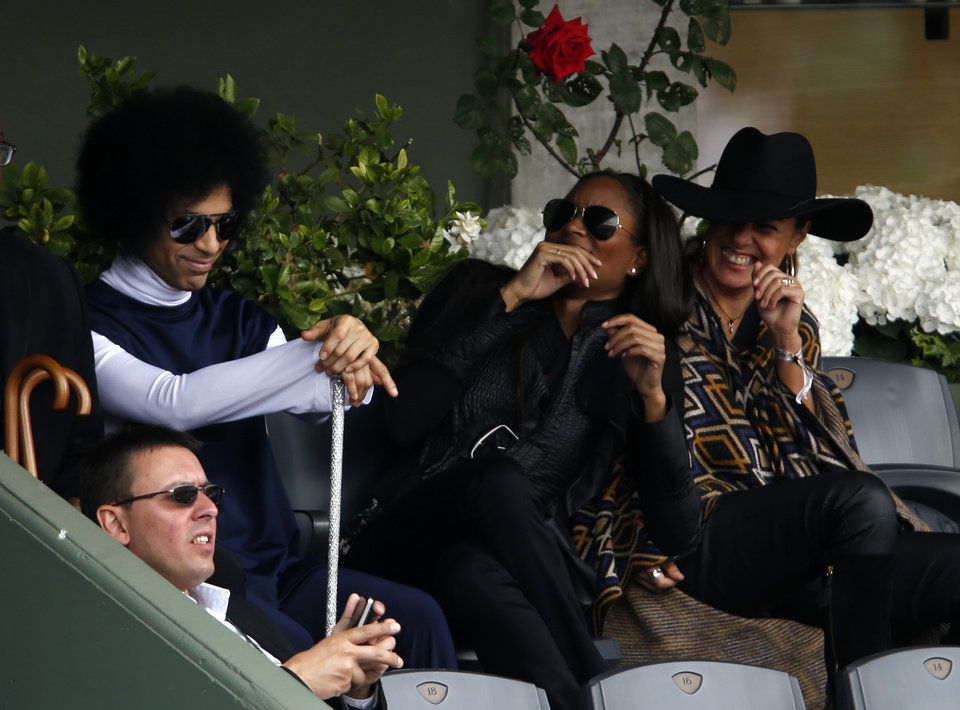 Photo - U.S pop singer Prince, top left and unidentified women, watch Spain's Rafael Nadal playing  Serbia's Dusan Lajovic during their fourth round match of  the French Open tennis tournament at the Roland Garros stadium, in Paris, France, Monday, June 2, 2014. (AP Photo/Darko Vojinovic)