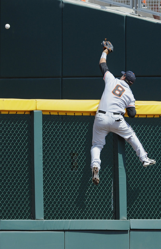 Photo - Oregon State left fielder Michael Conforto climbs the fence as he is unable to catch a three-run home run by Mississippi State's Hunter Renfroe during the fifth inning of an NCAA College World Series baseball game in Omaha, Neb., Friday, June 21, 2013.  (AP Photo/Eric Francis)