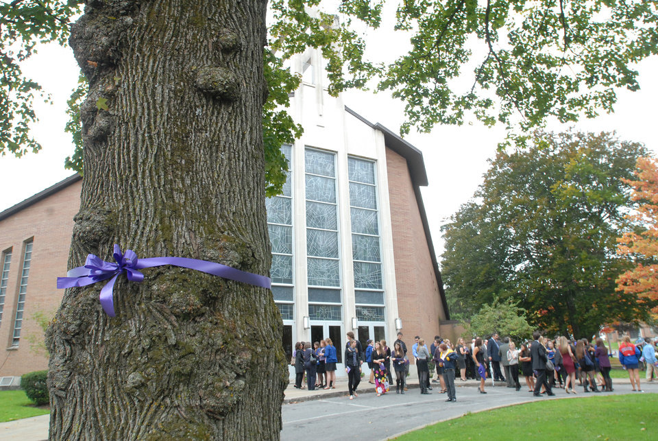 Photo -   A purple ribbon in support of stopping domestic violence is displayed on a tree in front of St. John the Evangelist Church at the funeral service for Alexandra Kogut, Monday, Oct. 4, 2012, in New Hartford, N.Y.Kogut's body was found early Saturday in her dorm room at the State University of New York College at Brockport, near Rochester. Her boyfriend Clayton Whittemore, of New Hartford, is charged with the killing. (AP Photo/Observer-Dispatch, Mark DiOrio)