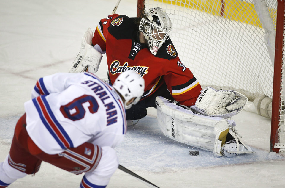 Photo - New York Rangers' Anton Stralman, left, from Sweden, has his shot stopped by Calgary Flames goalie Karri Ramo, from Finland, during the second period of an NHL hockey game in Calgary, Alberta, Friday, March 28, 2014. (AP Photo/The Canadian Press, Jeff McIntosh)