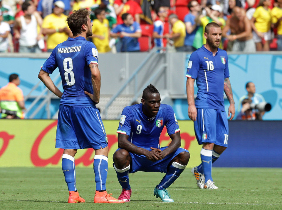 Photo - Italy's Mario Balotelli, center, and Italy's Claudio Marchisio react after Costa Rica's Bryan Ruiz scored the opening goal during the group D World Cup soccer match between Italy and Costa Rica at the Arena Pernambuco in Recife, Brazil, Friday, June 20, 2014.   (AP Photo/Antonio Calanni)