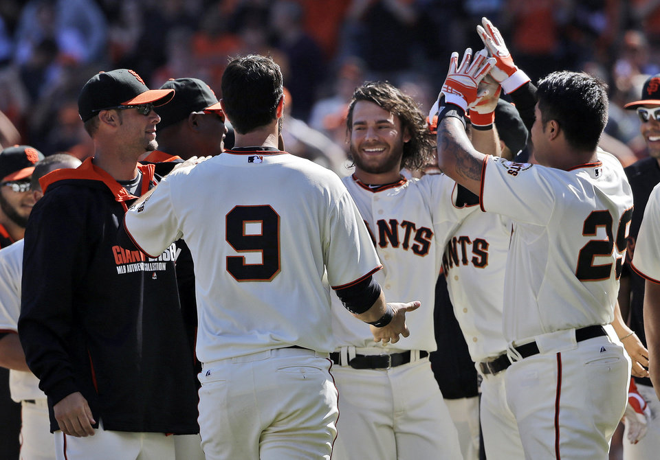 Photo - San Francisco Giants' Brandon Crawford, center, is greeted by teammates after his walk-off home run to beat the Colorado Rockies during the 10th inning of a baseball game on Sunday, April 13, 2014, in San Francisco. San Francisco won 5-4. (AP Photo/Marcio Jose Sanchez)