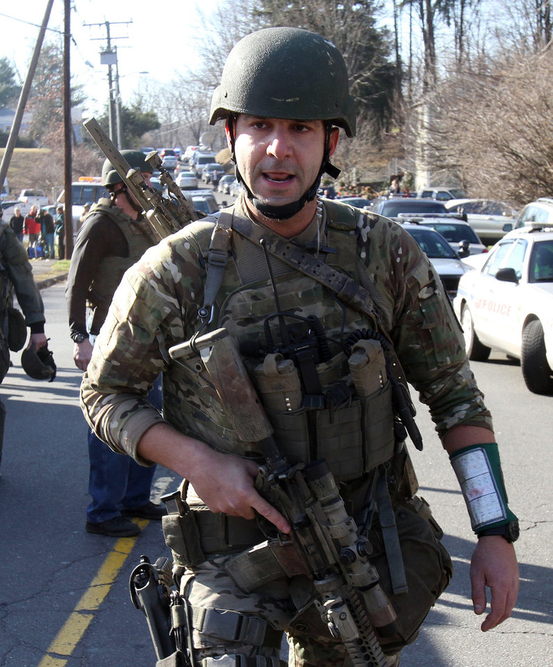 Photo - Heavily armed Connecticut State troopers are on the scene at the Sandy Hook School where authorities say a gunman opened fire, leaving 27 people dead, including 20 children, Friday, Dec. 14, 2012. (AP Photo/The Journal News, Frank Becerra Jr.) MANDATORY CREDIT, NYC OUT, NO SALES, TV OUT, NEWSDAY OUT; MAGS OUT ORG XMIT: NYWHI119