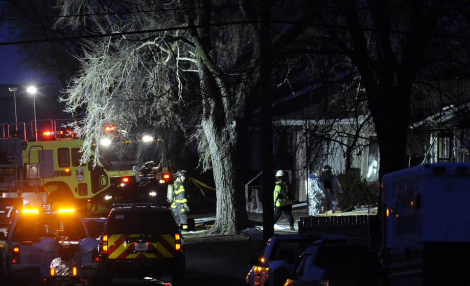 Photo - South Bend police and fire officials examine a home where a a plane crash occurred near the South Bend Regional Airport Sunday March 17, 2013 in South Bend, Ind. The private jet apparently experiencing mechanical trouble crashed in a northern Indiana neighborhood, resulting in injuries and striking three homes, authorities and witnesses said. (AP Photo/Joe Raymond)