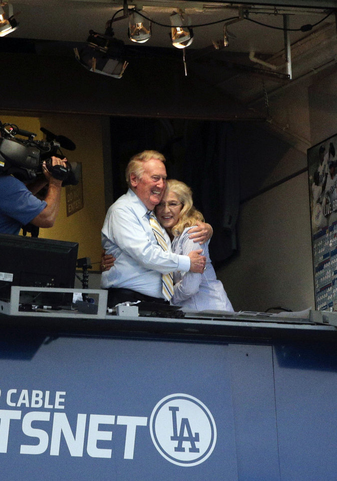 Photo - Broadcaster Vin Scully, left, embraces his wife, Sandi, at Dodger Stadium during a baseball game between the Los Angeles Dodgers and the Atlanta Braves on Tuesday, July 29, 2014, in Los Angeles. The Dodgers announced that Scully will remain with the team for the 2015 season. (AP Photo/Jae C. Hong)