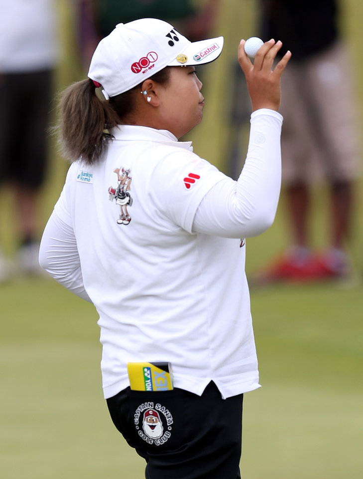 Photo - South Korea's Sun Ju Ahn holds up her ball after finishing her round as the leader on the third day of the Women's British Open golf championship at the Royal Birkdale Golf Club, Southport, England, Saturday July 12, 2014. (AP Photo/Scott Heppell)