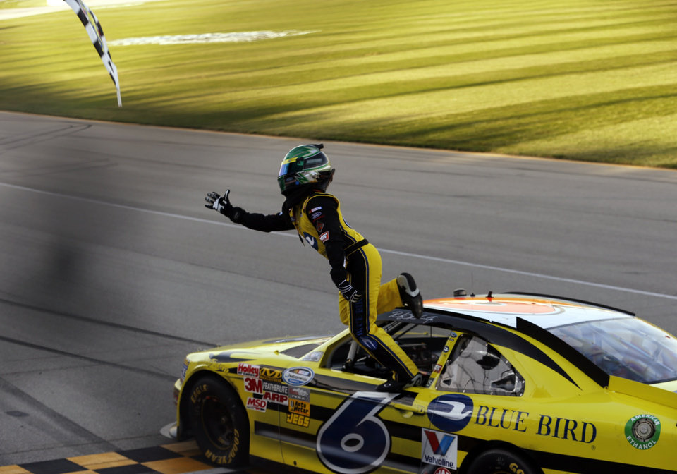 Photo -   Ricky Stenhouse Jr. reaches for the checkered flag after winning the NASCAR Nationwide Series auto race at Chicagoland Speedway in Joliet, Ill., Saturday, Sept. 15, 2012. (AP Photo/Tim Stewart)