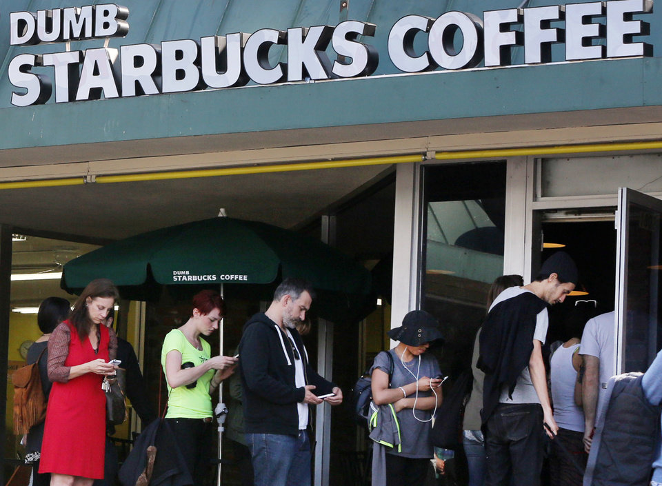 Photo - People line up at Dumb Starbucks coffee in Los Angeles Monday, Feb. 10, 2014.  The store resembles a Starbucks with a green awning and mermaid logo, but with the word