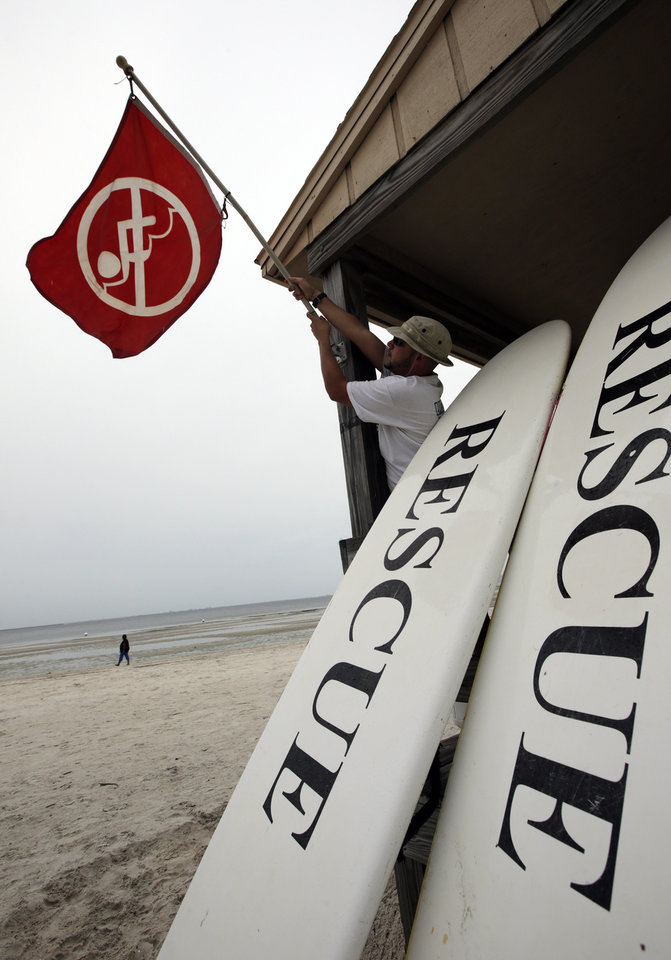 Lifeguard Duane Gonzalez takes down the red warning flag on a beach in Tampa, Fla., Sunday, Aug. 26, 2012.  Some rain and winds from Tropical Storm Isaac are beginning to reach Tampa where the Republican National Convention has postponed the start of their meeting because of the approaching storm. (AP Photo/Dave Martin) ORG XMIT: FLDM101