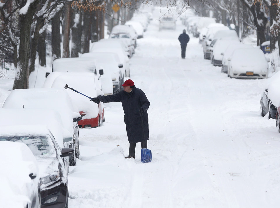 Photo - A man clears snow from a vehicle on Friday, Jan. 3, 2014, in Albany, N.Y.  A winter storm slammed into the U.S. Northeast with howling winds and frigid cold, dumping nearly two feet (60 centimeters) of snow in some parts and whipping up blizzard-like conditions Friday. (AP Photo/Mike Groll)