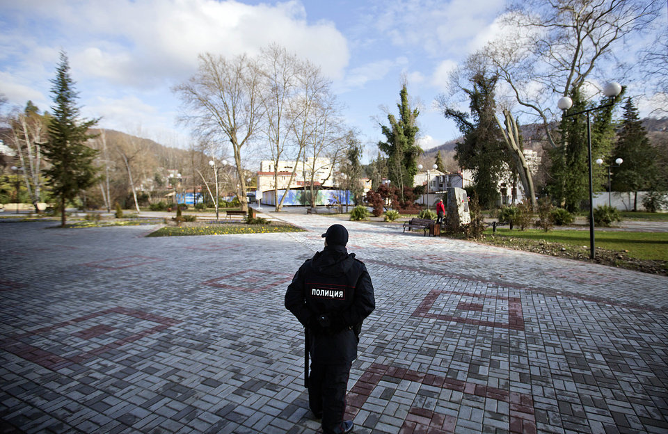 Photo - A police officer patrols though the 50 Years of Victory in the Great Patriotic War Park, the designated Olympic protest area for the 2014 Winter Olympics, in the Khosta district, Saturday, Feb. 1, 2014, in Sochi, Russia. (AP Photo/David Goldman)