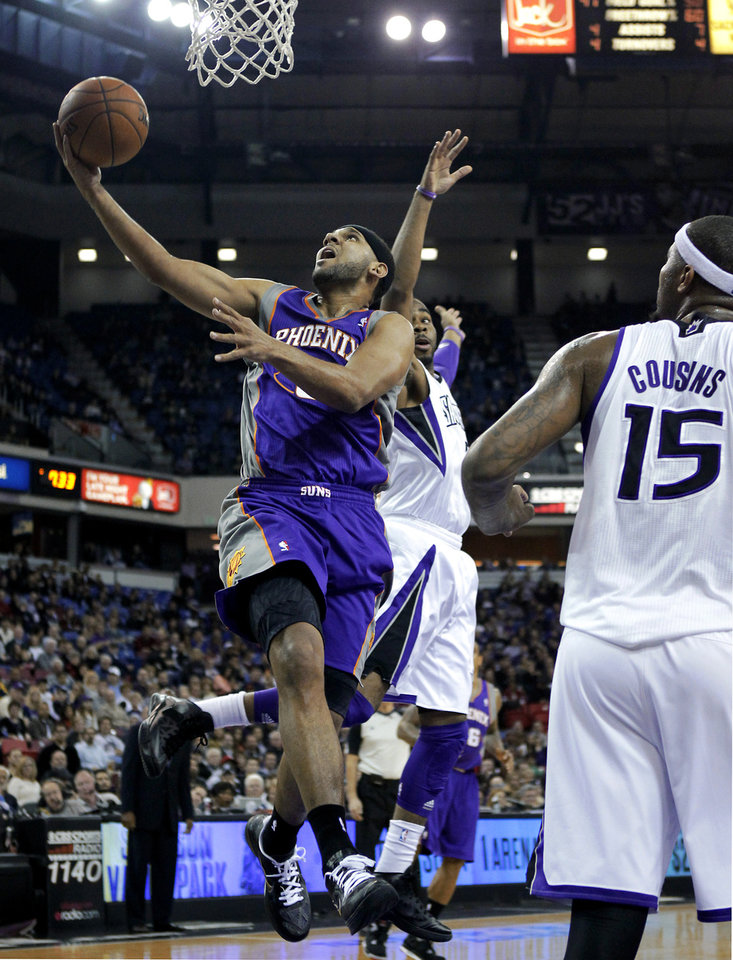 Phoenix Suns guard Jared Dudley, left, drives to the basket between Sacramento Kings' Marcus Thornton, center, and DeMarcus Cousins during the first quarter of an NBA basketball game in Sacramento, Calif., Wednesday, Jan. 23, 2013. (AP Photo/Rich Pedroncelli)