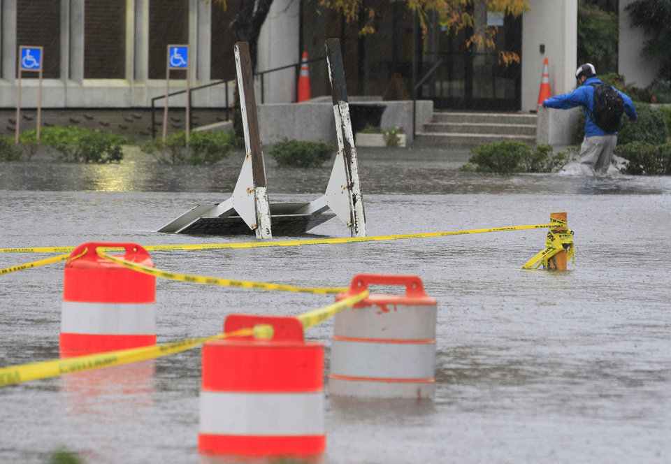 A Norfolk resident walks to work through floodwaters near downtown Norfolk, Va., Monday, Oct. 29, 2012. Rain and wind from Hurricane Sandy are hitting the area. (AP Photo/Steve Helber) ORG XMIT: VASH102