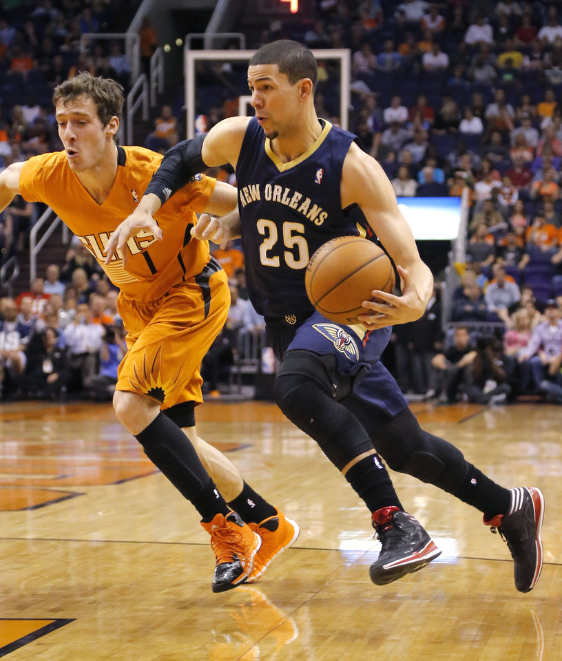 Photo - New Orleans Pelicans' Austin Rivers (25) drives past Phoenix Suns' Goran Dragic, of Slovenia, during the first half of an NBA basketball game, Friday, Feb. 28, 2014, in Phoenix. (AP Photo/Matt York)