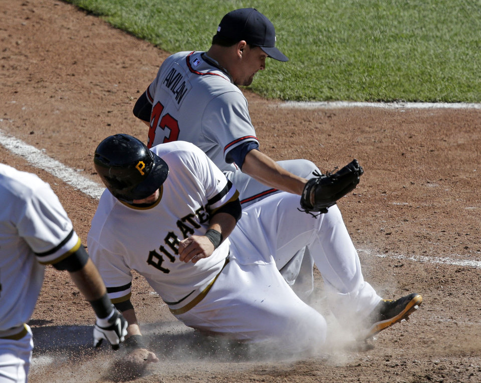 Pittsburgh Pirates base runner Travis Snider, front, scores on a wild pitch by Atlanta Braves relief pitcher Luis Avilan, rear, during the seventh inning of a baseball game in Pittsburgh Sunday, April 21, 2013. The Pirates won 4-2. (AP Photo/Gene J. Puskar)
