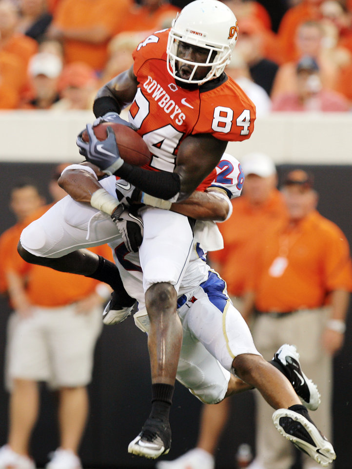 Photo - OSU's Hubert Anyiam (84) makes a touchdown catch as Lowell Rose (28) of TU defends in the first quarter during the college football game between the University of Tulsa (TU) and Oklahoma State University (OSU) at Boone Pickens Stadium in Stillwater, Oklahoma, Saturday, September 18, 2010. Photo by Nate Billings, The Oklahoman