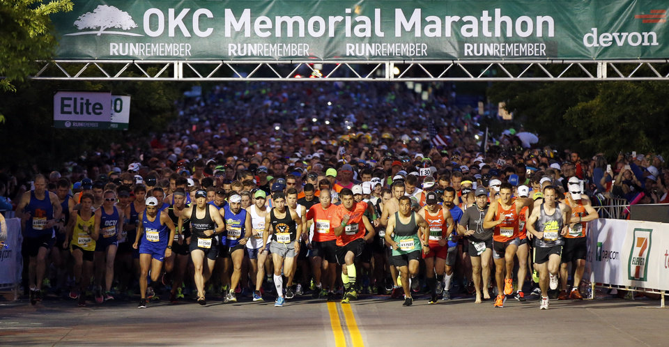 Photo - Runners begin the Oklahoma City Memorial Marathon going south on N. Harvey Ave. in downtown Oklahoma City, Sunday, April 24, 2016. Photo by Nate Billings, The Oklahoman
