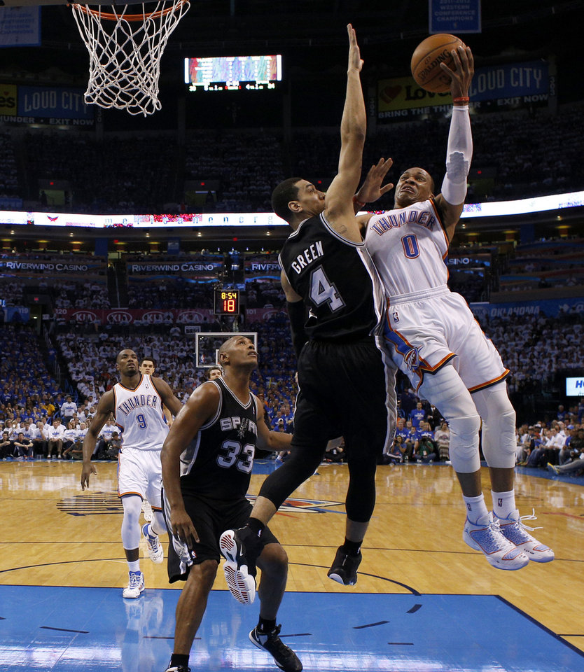 Photo - Oklahoma City's Russell Westbrook (0) goes to the basket beside San Antonio's Danny Green (4) and Boris Diaw (33) during Game 4 of the Western Conference Finals in the NBA playoffs between the Oklahoma City Thunder and the San Antonio Spurs at Chesapeake Energy Arena in Oklahoma City, Tuesday, May 27, 2014. Photo by Bryan Terry, The Oklahoman