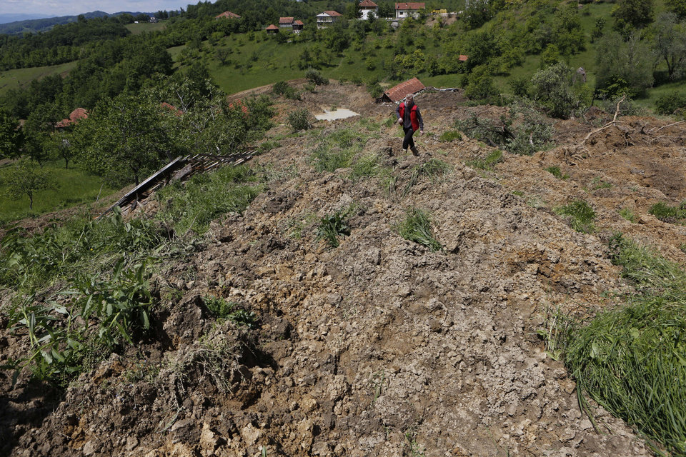 Photo - A Bosnian man walks on a broken road after a landslide which swept away eight houses near Kalesija, Bosnia, 150 kms north of Sarajevo, Sunday May 18, 2014. Packed into buses, boats and helicopters, carrying nothing but a handful of belongings, tens of thousands fled their homes in Bosnia and Serbia, seeking to escape the worst flooding in a century. (AP Photo/Amel Emric)
