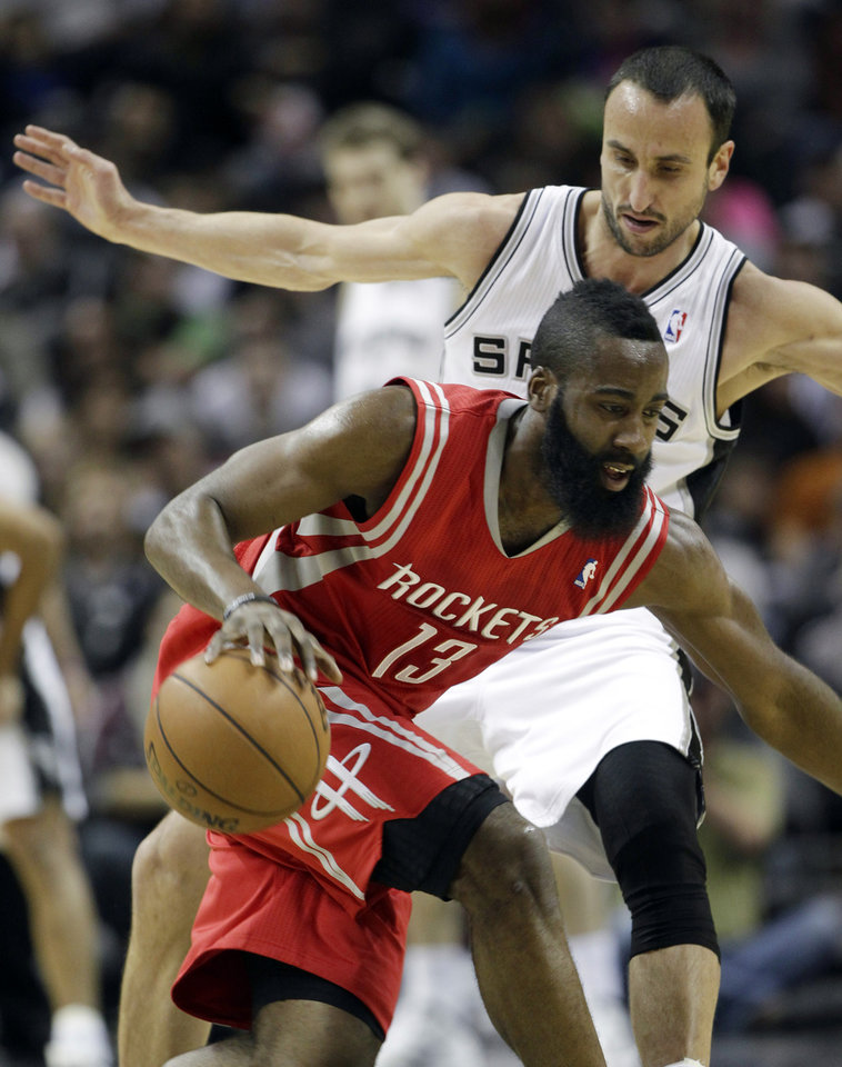 Photo - Houston Rockets' James Harden (13) tries ot move the ball around San Antonio Spurs' Manu Ginobili, right, of Argentina, during the first quarter of an NBA basketball game on Friday, Dec. 28, 2012, in San Antonio. (AP Photo/Eric Gay)