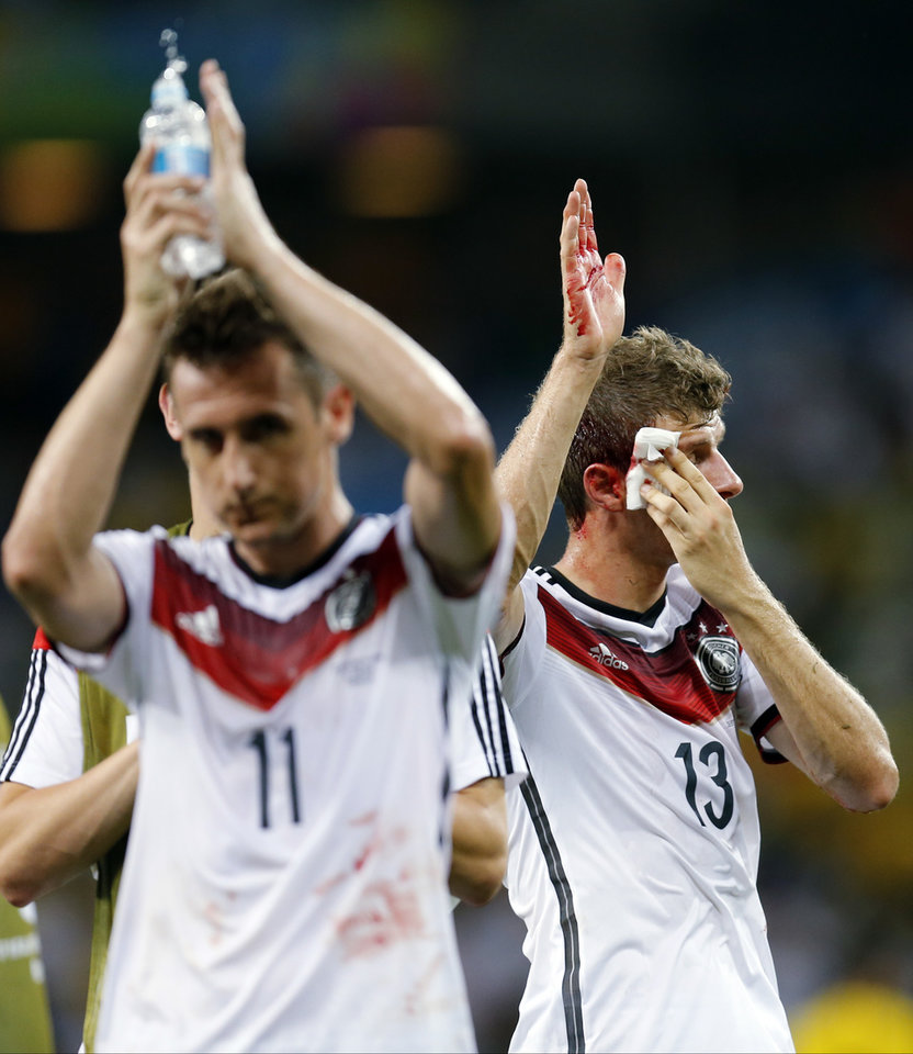Photo - Germany's Thomas Mueller, right, walks off the pitch with Miroslav Klose after Mueller was inured during the group G World Cup soccer match between Germany and Ghana at the Arena Castelao in Fortaleza, Brazil, Saturday, June 21, 2014. (AP Photo/Frank Augstein)