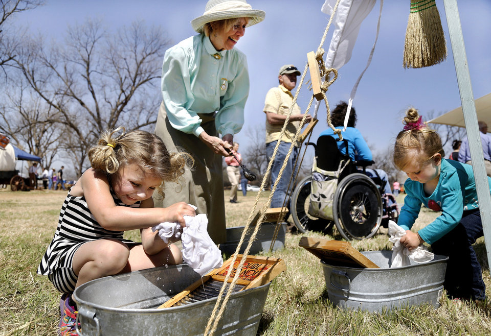 "Photo - Volunteer Mary McDonald explains the method of washing clothes in pioneer days as two small girls kneel beside a tub of water  washing pieces of fabric with  lye soap and a scrub board. After rinsing the soap from the fabric, McDonald would help children hang their ""clean laundry""  on a line with clothes pins. McDonald is with the Cherokee Strip Heritage Center in Enid. Oklahoma Cooperative Extension Service celebrated their 100th anniversary with a Whistle Stop and Festival on Saturday, April, 12, 2014 at the Rock 'N Rail yard near Highway 66 in Wellston, Oklahoma.  ""In the early 1900s, trains were the modern way to travel and early Extension agents were allowed to 'ride the rails', going from town to town presenting demonstrations  and showing people how they might improve the quality of their lives by making use of the latest science-proven advances, practices and products,"" said James Trapp. OCES associate director. A train coming into town was sometimes referred to  as a ""county fair on wheels."" As part of its centennial celebration, Extension conducted an historic reenactment  of the type of whistle stop tours that would have occurred   in 1914. Visitors  at the festival were given the opportunity to visit a variety of tents and booths offering demonstrations and hands-on activities representative of Extension programs. Photo by Jim Beckel, The Oklahoman"