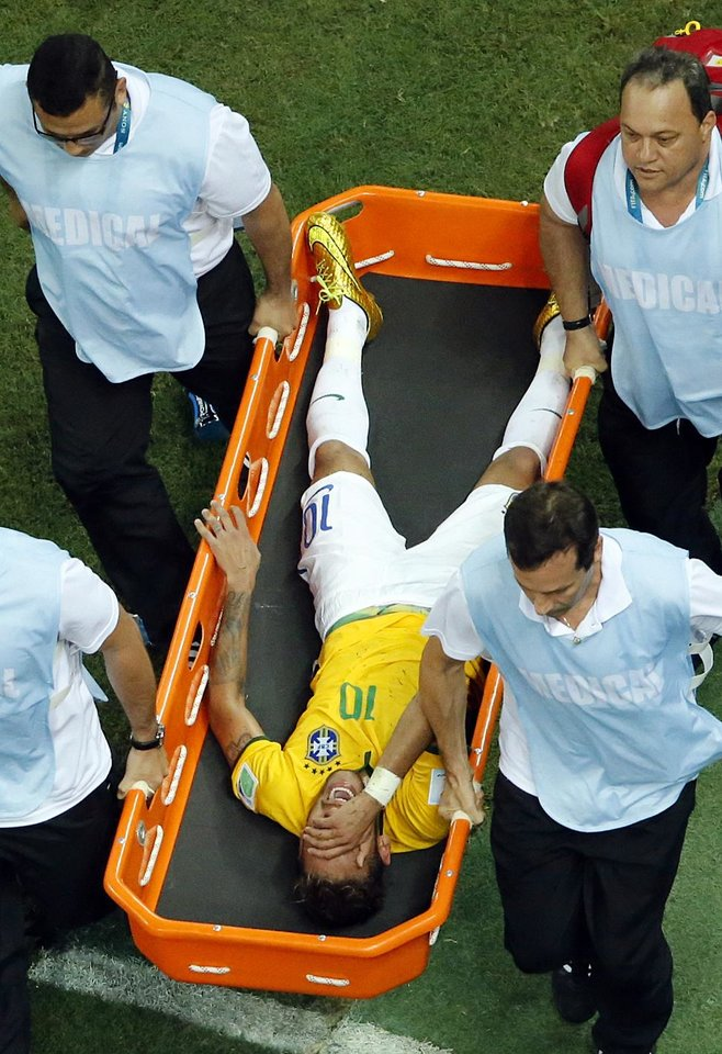Photo - Brazil's Neymar is carried away after getting injured during the World Cup quarterfinal soccer match between Brazil and Colombia at the Arena Castelao in Fortaleza, Brazil, Friday, July 4, 2014. (AP Photo/Fabrizio Bensch, pool)