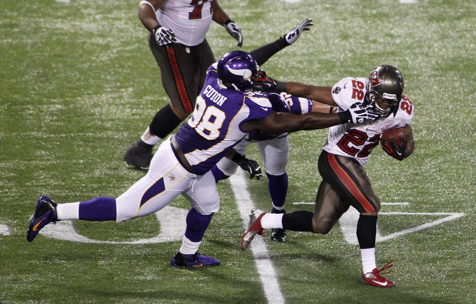 Photo -   Tampa Bay Buccaneers running back Doug Martin (22) breaks a tackle by Minnesota Vikings defensive tackle Letroy Guion (98) during a 64-yard touchdown reception in the second half of an NFL football game Thursday, Oct. 25, 2012, in Minneapolis. (AP Photo/Andy King)