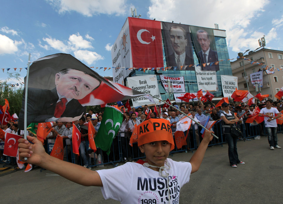 Photo - Supporters of Turkish Prime Minister Recep Tayyip Erdogan wave flags before he arrives to address a party rally outside Ankara, Turkey, Saturday, June 15, 2013. Erdogan said Friday he has asked a small delegation of protesters to convince those occupying a park to withdraw, adding that he is hopeful their protest action would end soon.(AP Photo/Burhan Ozbilici)
