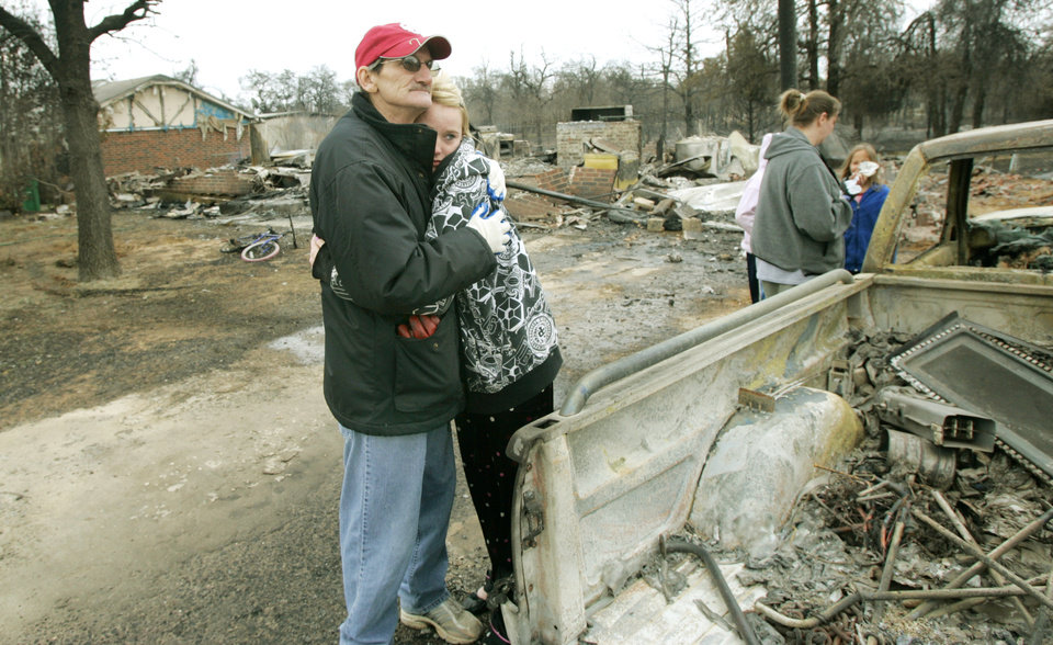 Photo - Oscar Green hugs his granddaughter Courtney Nelson,16 in front of his home at 14340 NE 4th after it was destroyed in a wildfire in Choctaw, Oklahoma April 10, 2009.  Photo by Steve Gooch, The Oklahoman