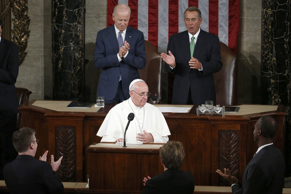 Photo - Vice President Joe Biden and House Speaker John Boehner of Ohio applaud Pope Francis after his address before a joint meeting of Congress on Capitol Hill  in Washington, Thursday, Sept. 24, 2015, making history as the first pontiff to do so. (AP Photo/Carolyn Kaster)