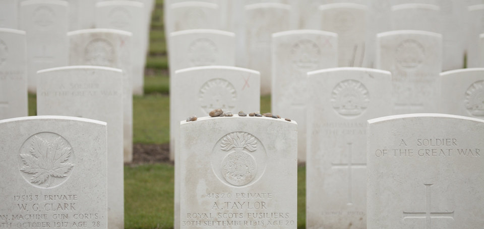 Photo - Stones are left as a memento atop a WWI soldiers grave at Tyne Cot cemetery in Zonnebeke, Belgium on Monday, April 15, 2013. With nearly 12,000 graves the cemetery is the largest Commonwealth war cemetery in the world in terms of burials. Renovations are currently underway at the cemetery to accommodate visitors for upcoming centenary events which begin in 2014. (AP Photo/Virginia Mayo)