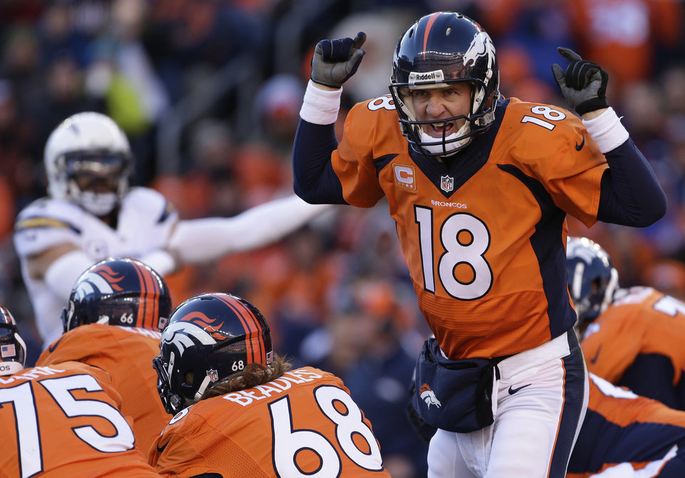 Photo - Denver Broncos quarterback Peyton Manning (18) calls an audible at the line of scrimmage against the San Diego Chargers in the first quarter of an NFL AFC division playoff football game, Sunday, Jan. 12, 2014, in Denver. (AP Photo/Charlie Riedel)