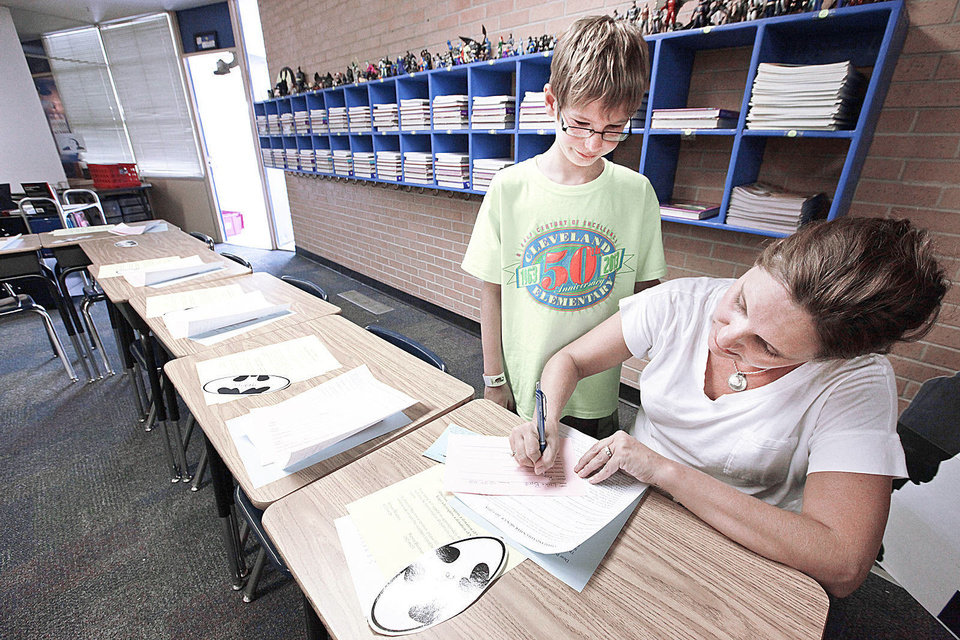 Photo - Fifth-grader Luke Byrd and his mom, Dava, fill out paperwork on his desk during back-to-school night at Cleveland Elementary School in Norman, Monday , August 19, 2013. Photo by David McDaniel, The Oklahoman